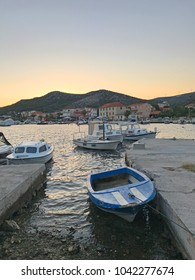 White boat in small Croatian marina at sunset