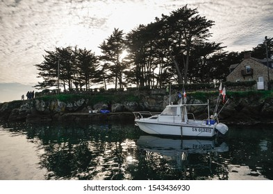 White boat standing in a harbor of Atlantic ocean. Reflection in water