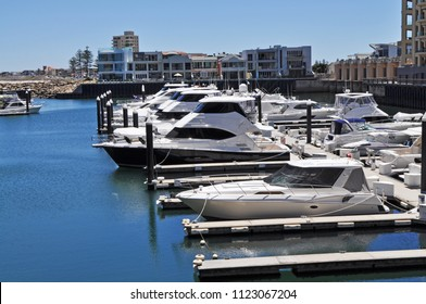 White boats parked in the Glenelg Marina, on the calm water on the sunny day. Adelaide, South Australia