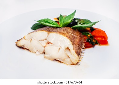white boiled fish halibut with vegetables on a plate isolated