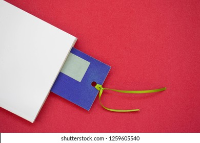 White book and a blue bookmark on a red background