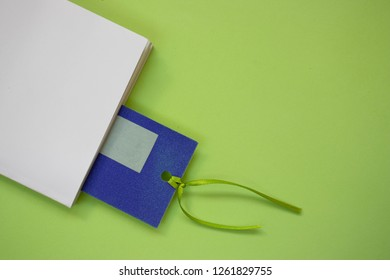 White book with a bookmark on a green background