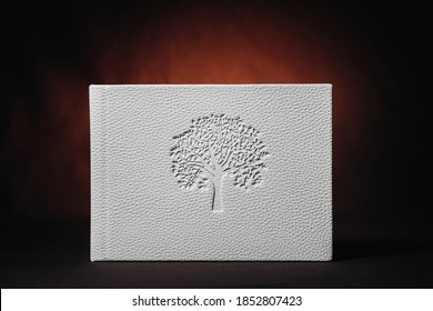 White book in genuine white leather on a dark embossed background . White paper on a dark background.