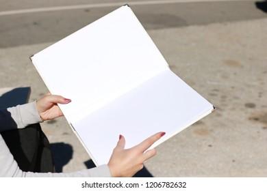 White book in hand