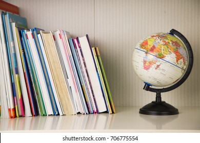 White book rack with many colorful books and small globe on black stand. Back to school, alarm clock and sketch pen set, horizontal view, with books for kids in room for children