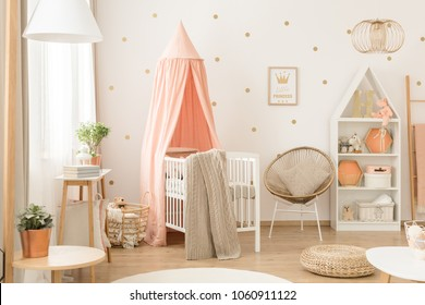 White bookcase with plush toys and decorations in a cute, cozy, white and peach pink scandinavian nursery interior