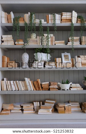 White Books And Vintage Objects On A Light Gray Wood Bookshelf