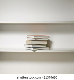 white bookshelf in three rows with few books in the middle