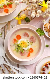 White borscht, polish Easter soup with the addition of white sausage and a hard boiled egg in a ceramic bowl, top view. Traditional Easter dish in Poland