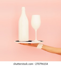 White bottle and glass on a tray. fashion design