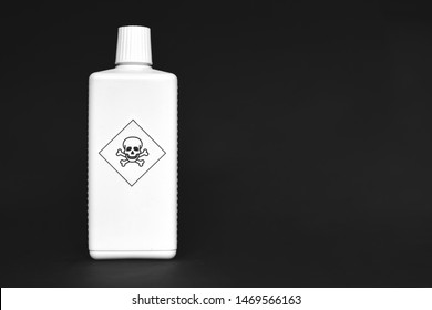 White bottle with poison warning signs on them on black background