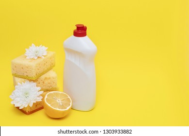 White bottle of soap standing near sponges with flowers and lemon isolated on yellow background