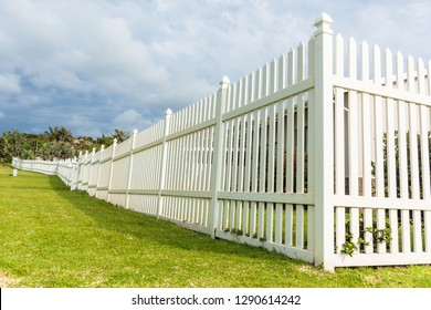 White boundary vertical slat plastic pvc fence along roadside grass landscape.