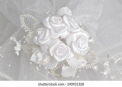 White boutonniere on bridal veil on gray background