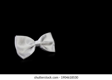 White bow tie on black background. An element of the men's wardrobe. Free space for copying.