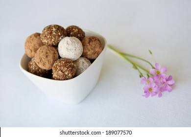 A white bowl of an assortment chocolate balls and rum balls presented with a purple flower on a white background.