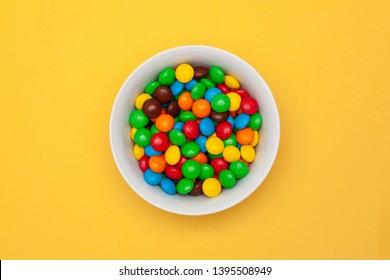 White bowl with chocolate colored round candy on yellow background in the center. Top view.