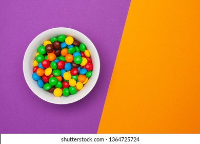 White bowl with chocolate round colored candies on a purple background with an orange place for the text.