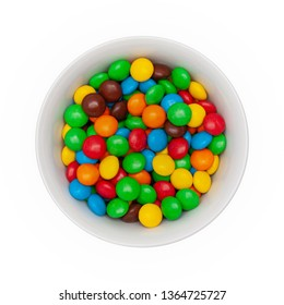White bowl with chocolate round colored candies on a white background. Isolated. Top view.