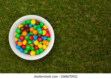 White bowl with chocolate round colored candies on a green grass with a place for the text.