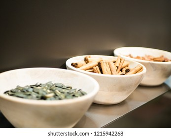 white Bowl of Cinnamon standing on a modern kitchen shelf, with other bowls and ingredients out of focus