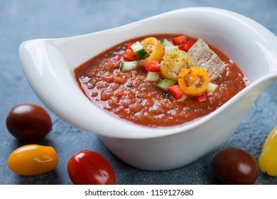 White bowl with cold gazpacho soup over blue stone background, horizontal shot, close-up