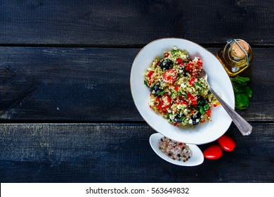 White bowl of delicious quinoa salad with feta cheese, cherry tomatoes, avocado, black olives on dark rustic wooden background, top view. Detox, dieting, vegan, vegetarian, clean eating concept