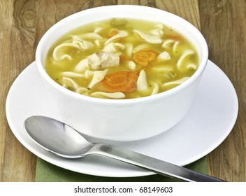 a white bowl filled with Delicious homemade chicken noodle soup