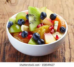 White bowl of fresh healthy fruit salad on wooden background