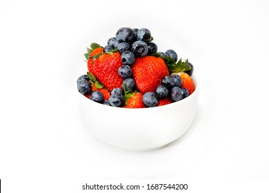 A white bowl full of delicious seasonal fruits, Blueberries and Strawberries, mixed together. In a white background. A perfect healthy breakfast or snack, vegan, and full of vitamins.