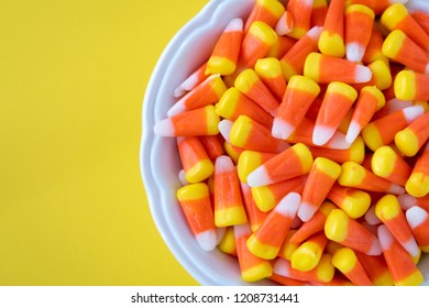 White bowl full of Halloween candy corn on a yellow background
