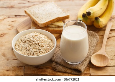 White bowl full of healthy oatmeal, with banana, milk, and dry bread for breakfast.