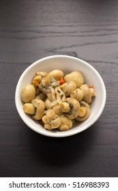 A white bowl full of marinated mushrooms.