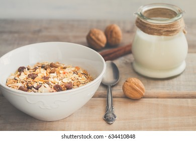 White bowl with Granola or Muesli and a jar of milk or plain yogurt and a spoon on a vintage wood background. Healthy breakfast composition.