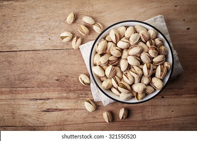 White bowl of pistachios on wooden background