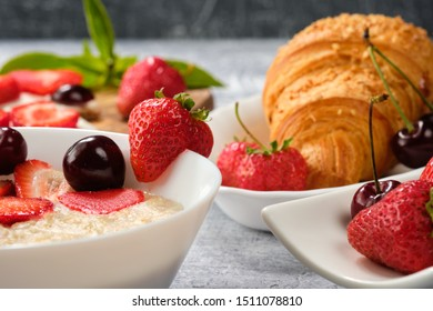 white bowl of porridge with strawberries and cherries, croissants and crispbread with cheese and strawberries on a gray background