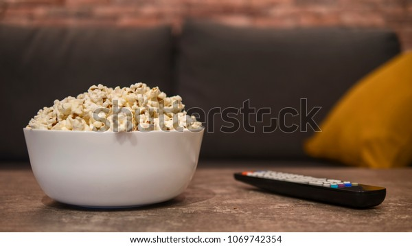 White bowl of white salty popcorn and remote control on a wooden table in front of a couch. Front view, blurry background