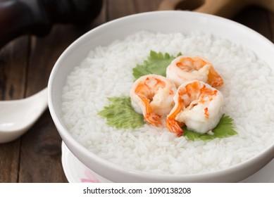 white bowl of Shrimp porridge, Thai rice soup with shrimp (Khao Tom Koong) on wood