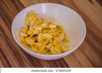 White bowl with small yellow banana pieces on a wooden table