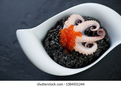 White bowl with squid-ink risotto over black stone background, view from above