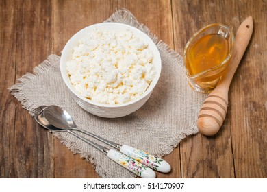 White bowl of tasty cottage cheese with milk and honey on wooden table