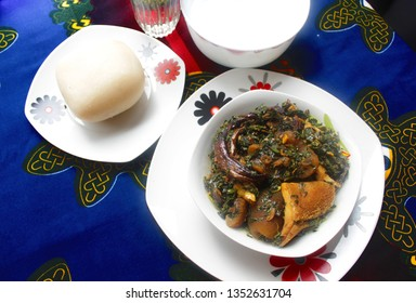 A white Bowl of Thick Vegetable Soup served with Dried Fish, Cow Skin Meat (Nigerian Kpomo), Cow Belly Meat (Nigerian Shaki) and Fufu on a Colorful Blue and Red Table Cloth - Top View