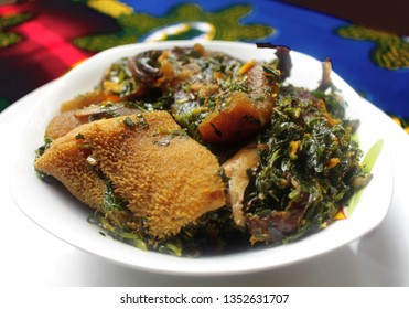A white Bowl of Thick Vegetable Soup served with Dried Fish, Cow Skin Meat (Nigerian Kpomo), Cow Belly Meat (Nigerian Shaki) placed on a Colorful Blue Table Cloth - Close Up View
