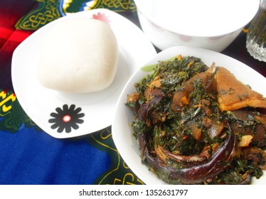 A white Bowl of Thick Vegetable Soup served with Dried Fish, Cow Skin Meat (Nigerian Kpomo), Cow Belly Meat (Nigerian Shaki) and Fufu on a Colorful Blue and Red Table Cloth
