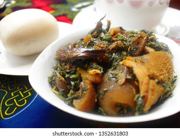 A white Bowl of Thick Vegetable Soup served with Dried Fish, Cow Skin Meat (Nigerian Kpomo), Cow Belly Meat (Nigerian Shaki) and Fufu on a Colorful Blue and Red Table Cloth - Close Up View