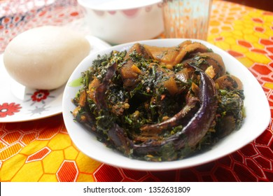 A white Bowl of Thick Vegetable Soup served with Dried Fish, Cow Skin Meat (Nigerian Kpomo), Cow Belly Meat (Nigerian Shaki) and Fufu on a Colorful Yellow and Red Pattern Table Cloth - Close Up View