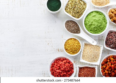 White bowls of various superfoods on white wooden  background