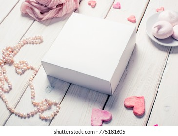 White box mockup next to different heart shapes and sweets