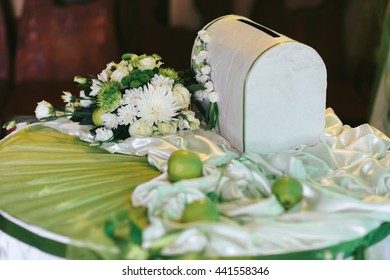 White box for the present envelopes stands on the white table decorated with flowers and apples