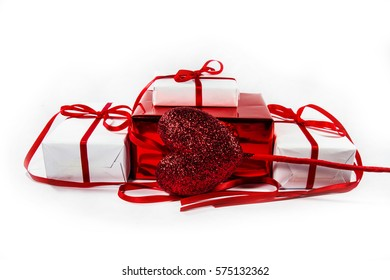White box with a red bow on a bright red rose petals on a white